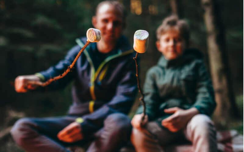 Monitor de acampamento comendo marshmallow ao redor da fogueira